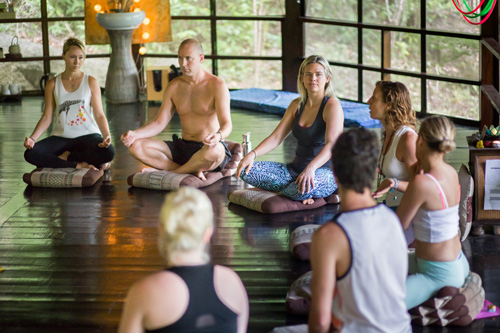 Students sitting on a shala floor at a yoga teacher training in Koh Phangan, Thailand