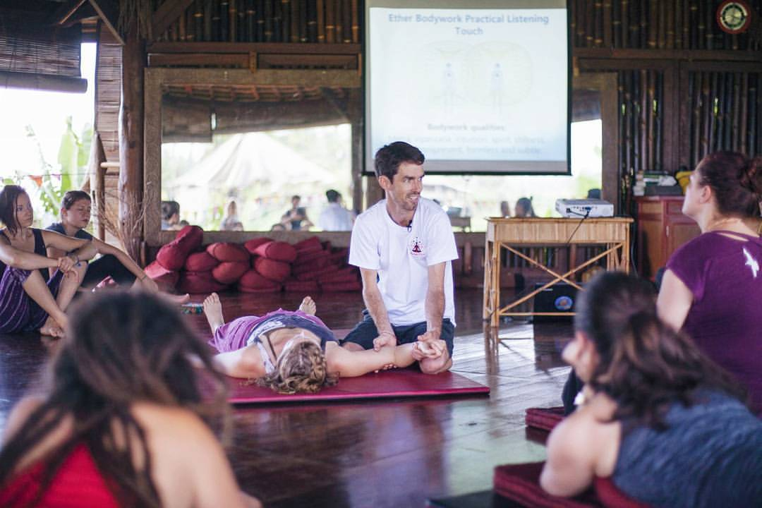Yoga teacher demonstrating on a student during a teacher training