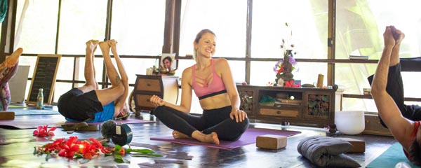 A student smiling while leading a class during a yoga teacher training